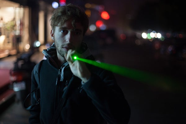 A photo of man shinning his laser pointer on the street at night