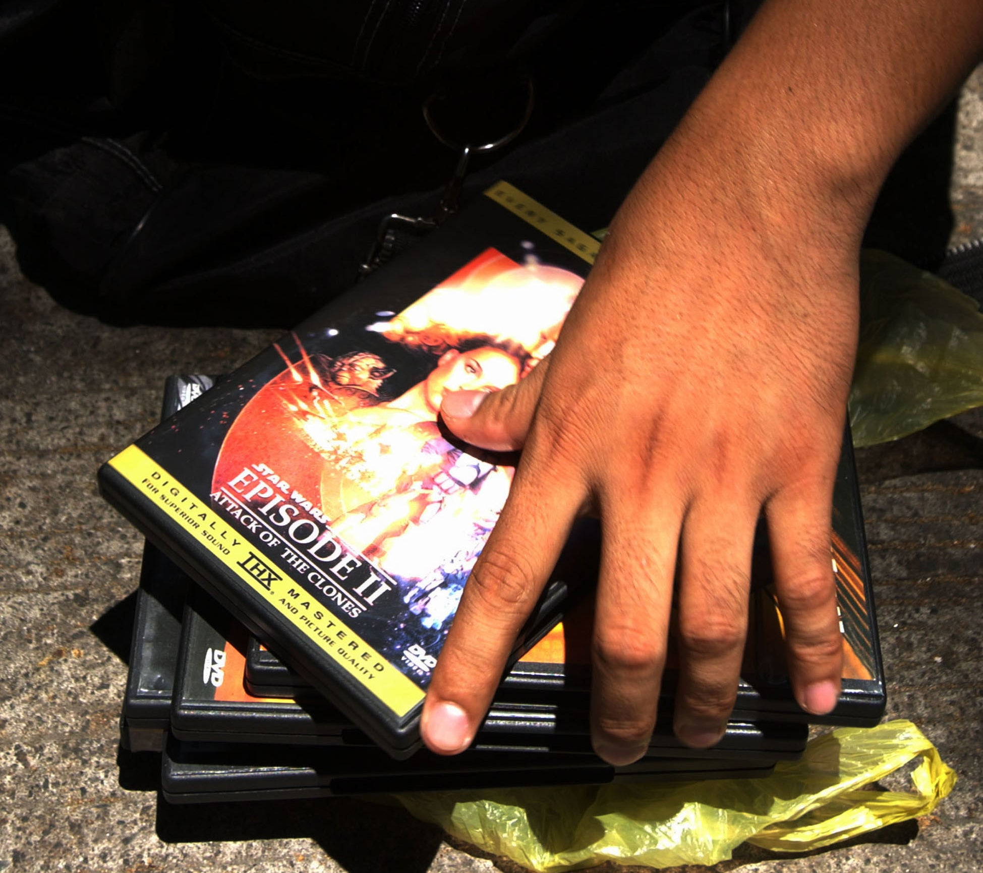 A hand holding several bootleg DVDs