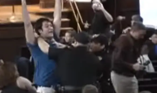 A man lifting his arms while being held down by cops